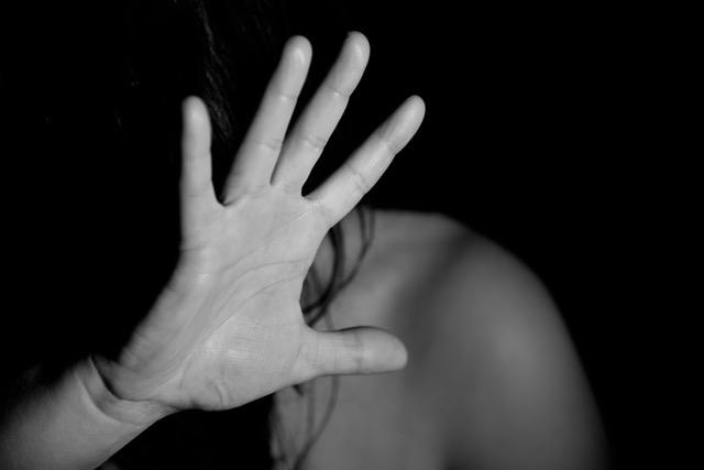 Žena zakrývajúca si tvár rukou, cíti strach.