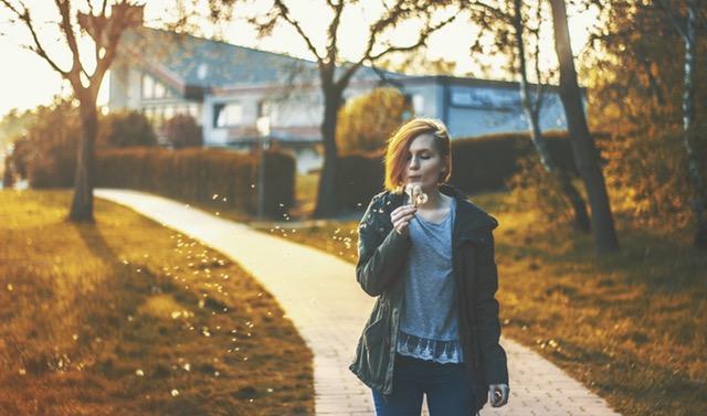 Mladá žena naulici, je jeseň, vpozadí vidieť oranžové lístie nazemi. Žena fúka do bublifuku.