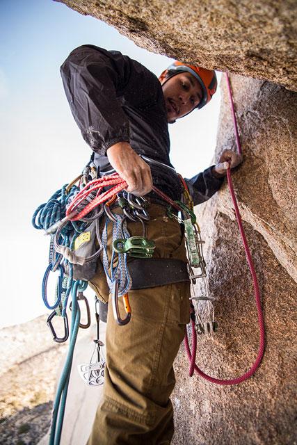 Horolezec naskale, natvárí sa mu zračí sústredenie, ale istrach.
